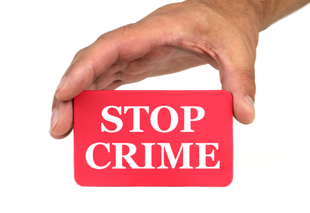 card stop: Hand holding and showing a red card with  STOP CRIME  text Stock Photo
