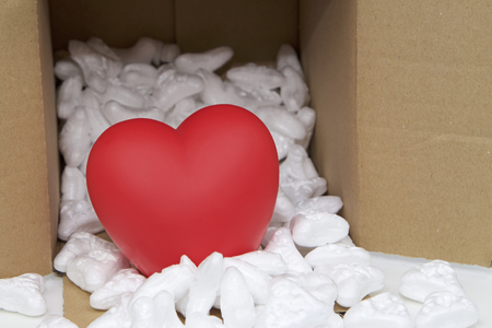 Red heart in mail package box with styrofoam. Conceptual image. Zdjęcie Seryjne