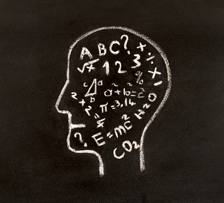Hand drawing human head shape with chalk  on blackboard and various formulas