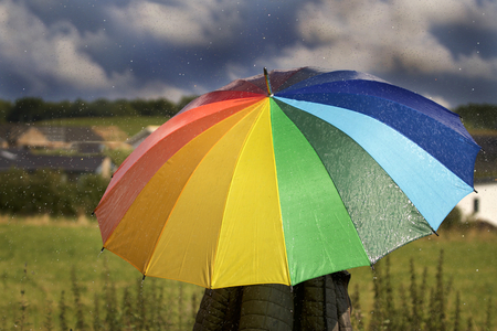A person with rainbow colored umbrella in the rain Stock fotó