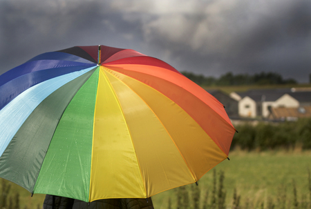 A person with rainbow colored umbrella under storm clouds
