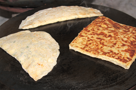 Turkish Gozleme.  Gozleme is a traditional Turkish dish featuring flat bread stuffed with a range of delicious fillings. Baked on sheet iron. Stock fotó - 116370981