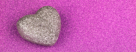 Shiny purple glitter paper and heart shape texture background. 免版税图像