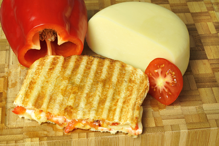 Toast with cheese , tomato and red bell peeper.