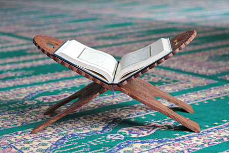 Quran on a wooden stand in mosque. Quran is holy book religion of Islam 스톡 콘텐츠