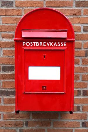Danish red mailbox on brown brick wall Stock Photo