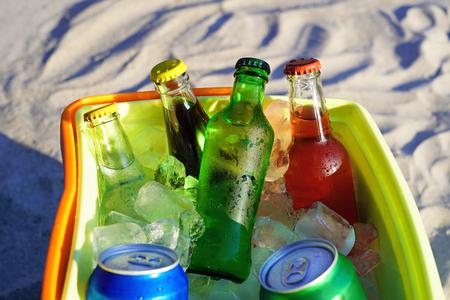 Bebidas gaseosas y cubitos de hielo llenos en una nevera portátil en la arena de la playa. Foto de archivo