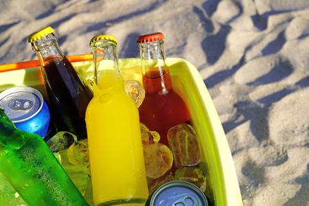 Colorful soda drinks and filled ice cubes in a coolbox on the beach sand.