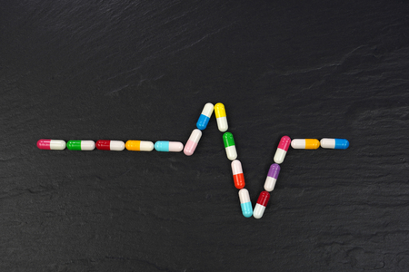 ECG graph with Colorful medical capsules on black background. Conceptual image.