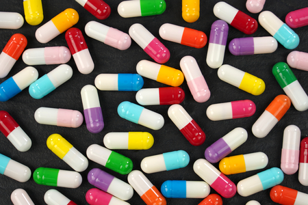 Colorful medical capsules on black background .