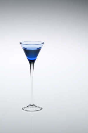 cordial: Blue cordial, aperitif, or liqueur glass with stem reflecting, off-center to left of frame. Stock Photo