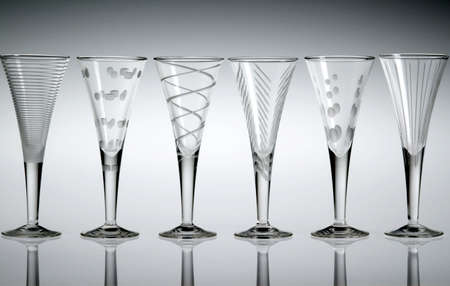 Six empty etched crystal liqueur glasses in a row, with a gray background. Imagens