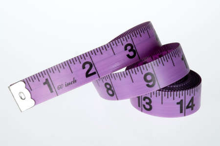 Measuring tape, purple and black, for sewing uncoiled on a white background.