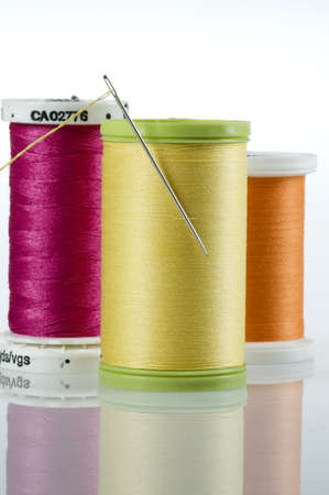 darn: Threaded needle stuck in a spool of yellow thread, surrounded by pink and orange spools.