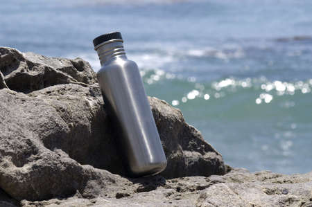 Stainless steel water bottle on a rock with the ocean in the background. Imagens