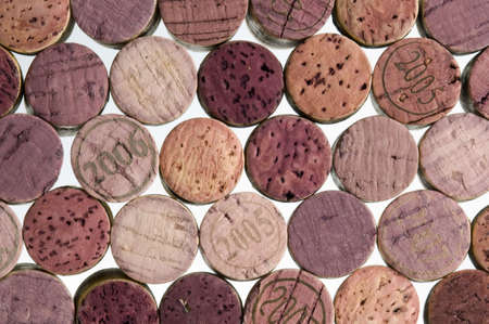 Wine corks, stained, fill the frame with a white background.
