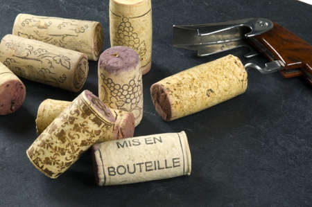 Wine corks and opener on a slate background, mis en bouteille printed. Imagens