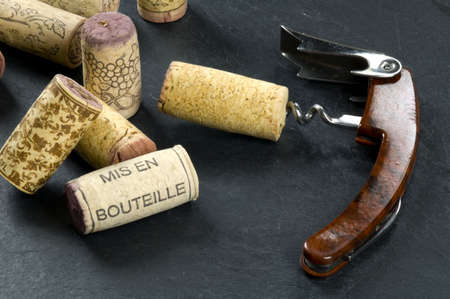 Wine corks and opener on a slate background, mis en bouteille printed Imagens