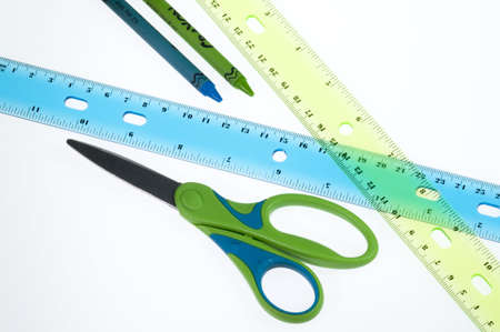 Blue and green scissors, crayons and rulers.