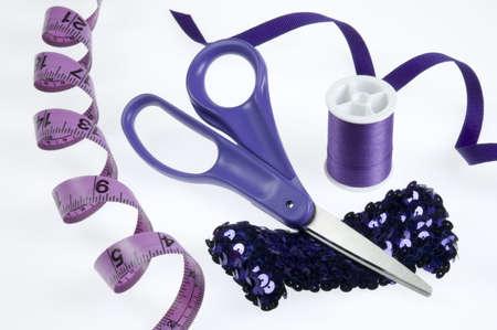 白い背景の上の紫の縫う用具。 写真素材