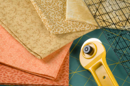 cutter: Quilting supplies: orange materials, rotary cutter, pad and ruler.