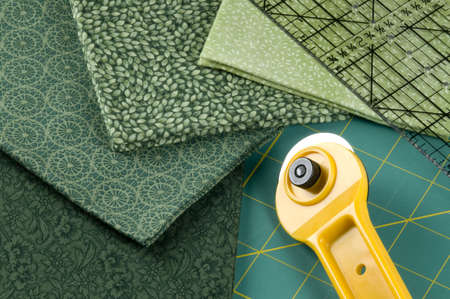 Quilting supplies: green materials, rotary cutter, pad and ruler. Imagens