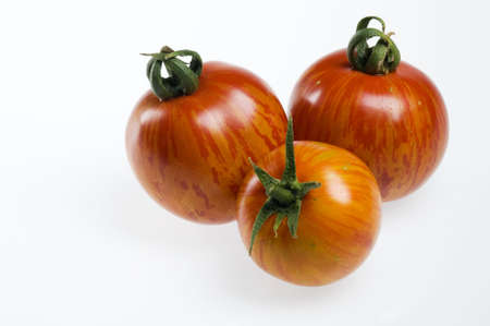 Three red zebra heirloom tomatoes on white background. Imagens