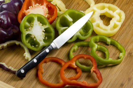 Knife leaning on sliced white, green, red and purple bell peppers. Imagens