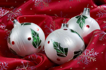 Three white balls decorated with holly leaves and berries sit on silky red material covered in snowflakes. Imagens