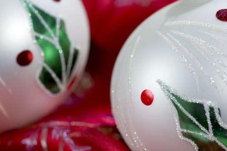 Macro shot of two Christmas ornaments adorned with holly leaves and berries.