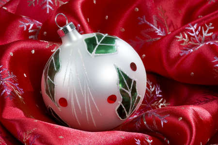 White Christmas ball decorated with green leaves and holly berries sits on silky red cloth covered in snowflakes.