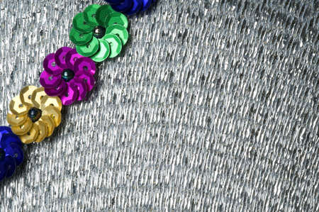 Silver textured background, with a diagonal embellishment of blue, gold, green and pink sequin flowers.