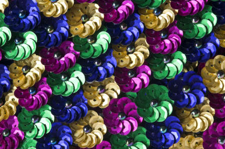 Close shot of green, gold, blue and fuschia sequin flowers create a vibrant background.