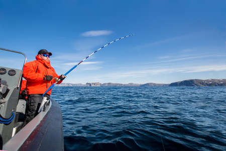 powerful man with a spinning rod in his hands. sea boat. fisherman Stock Photo