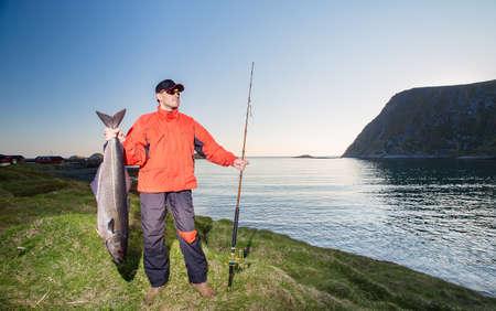 Visser is een atleet met een spin en trofee. grote vis. Avond. Noorwegen Stockfoto