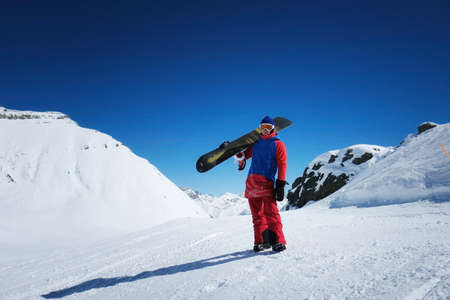 male sportsman snowboarder stands against the background of mountains. holds on his shoulder a snowboard board Stock Photo