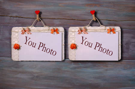 two photo paper attach to rope with clothes pins on wooden background