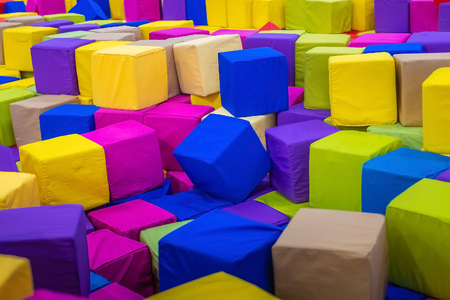 A young man or boy, father playing and jumping in soft cubes in the dry pool of the game childrens room for birthday. entertainment centre. indoor playground in foam rubber pit in trampoline.