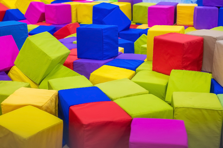 Many colorful soft blocks in a kids pool at a playground. Bright multi-colored soft cubes, geometric toys. Multicolored background.
