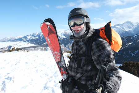 Freerider skier with skis in hand is smiling, portrait, 스톡 콘텐츠