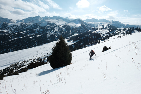 skier descends through the snow against the backdrop of the mountains.