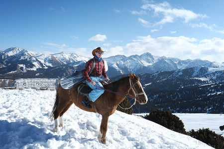 A man is a cowboy on a horse. Winter. the mountains