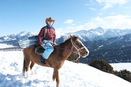 A man cowboy rides through the snow on a horse. Winter. the mountains. 스톡 콘텐츠