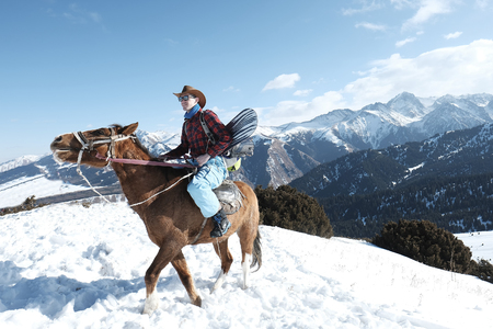 A man wearing a hat with a hat is riding a horse in the snow. Winter. the mountains.