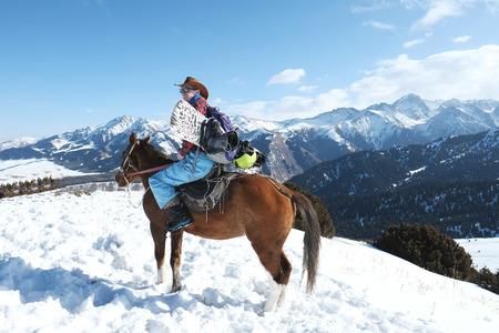 A man in a cowboy hat riding a horse in the snow. Winter. the mountains