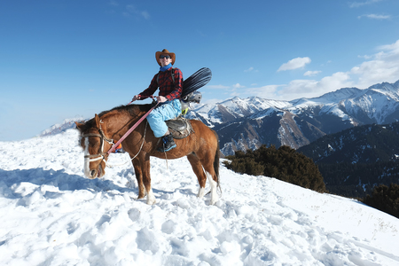 Freeride on horseback. A man in a cowboy hat riding a horse in the snow. Winter. the mountains. 스톡 콘텐츠