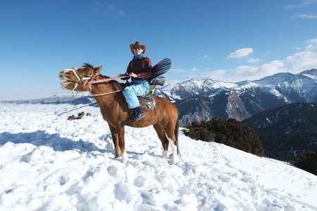 Snowboarder on a horse. Freeride. A man in a cowboy hat riding a horse in the snow. Winter. the mountains.
