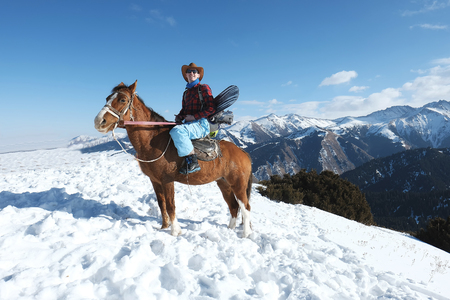 Freeride. A man in a cowboy hat riding a horse in the snow. Winter. the mountains.