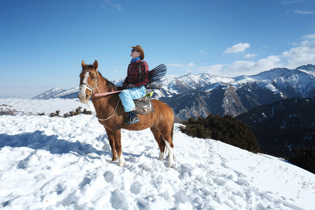 extreme snowboarder. Freeride. A man in a cowboy hat riding a horse in the snow. Winter. the mountains. 스톡 콘텐츠