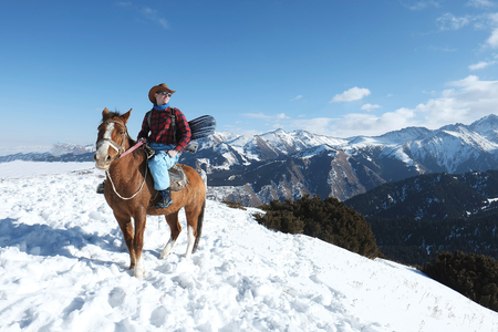 extreme snowboarder. Free rider A man in a cowboy hat riding a horse in the snow. Winter. the mountains. 스톡 콘텐츠